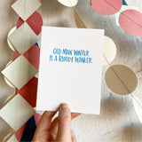 "white greeting card with blue hand-lettering that reads ""old man winter is a bloody wanker"" being hand-held in front of colorful paper garlands"