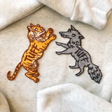 tuff tiger and tuff wolf patches photographed together on a grey sweatshirt