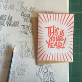 "white greeting card with red lines and hand-lettering that reads ""this is your year!"" photographed with design sketches"