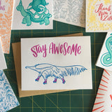"white greeting card with an illustrated ant-eater on rollerskates beneath hand-lettering that reads ""stay awesome"" photographed amongst other frog & toad press cards"