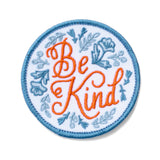 "A circular iron on patch with blue floral and a coral script that reads ""be kind""."