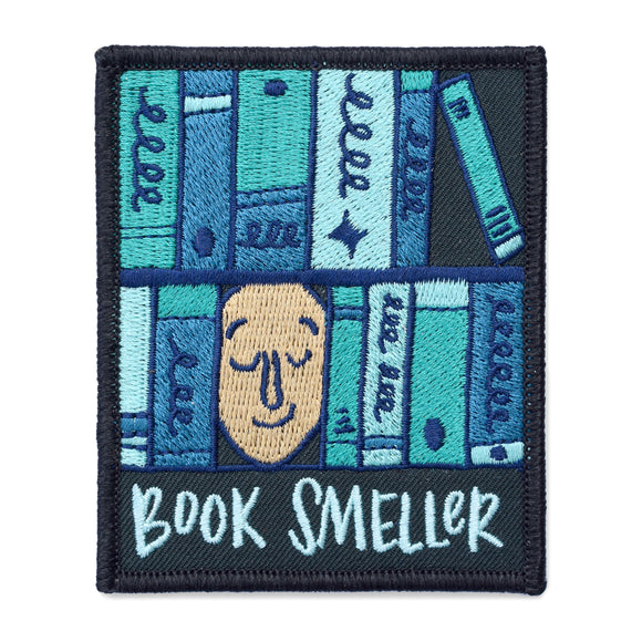 A rectangle patch with a face surrounded by various shades of blue books with text under it that says,