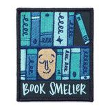 "A rectangle patch with a face surrounded by various shades of blue books with text under it that says, ""book smeller"" on a white background."