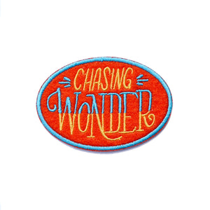 "An oval shaped red patch with ""chasing wonder"" in yellow and blue against a white background."