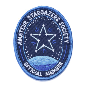 "An oval iron on patch that reads ""amateur stargazer society official member"" with a star connected like a constellation above a planet."
