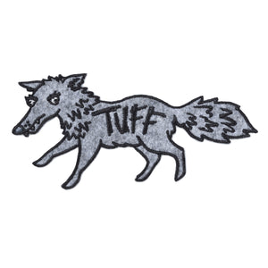 "grey fabirc patch in the shape of a wolf with the word ""tuff"" embriodered in it's middle"