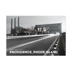 "black and white postcard photograph of night-time traffic driving over a downtown providence bridge with the iconic power station smoke stacks visable in the background. white text on the bottom reads ""greetings from providence, rhode island"""