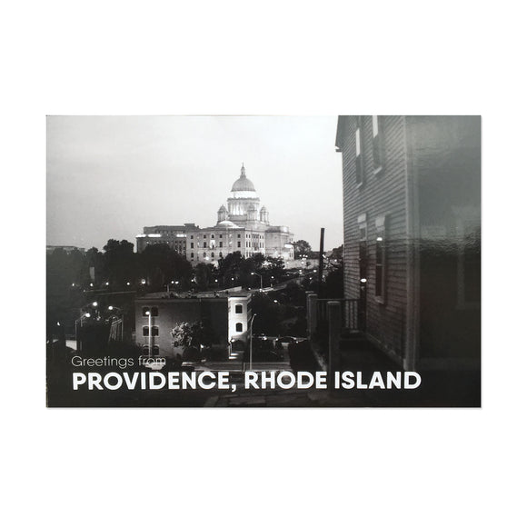 postcard of a black and white photograph of the RI state house at night behind some buildings and trees. white text reads