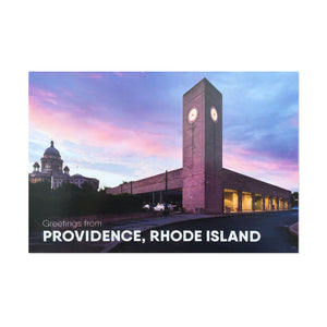 "postcard photograph of the providence train station at dusk with the state house visable in the background. white text at the bottom reads ""greetings from providence, rhode island"""