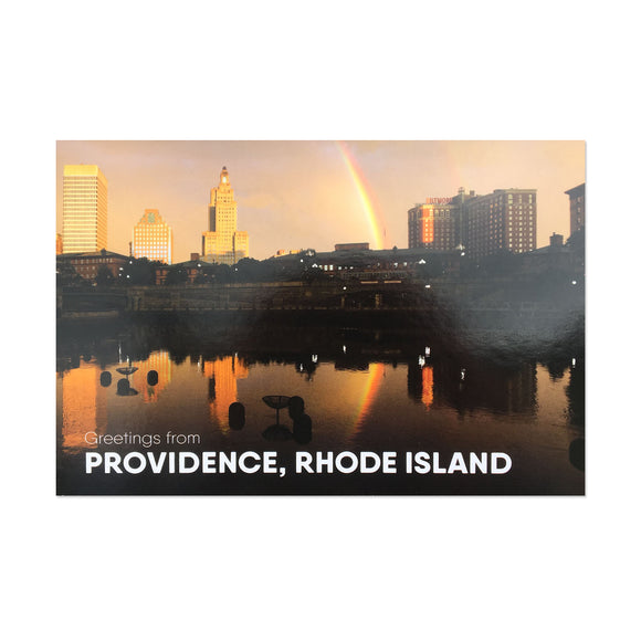 postcard phtoograph of the Providence skyline with a rainbow and white text on the bottom reading