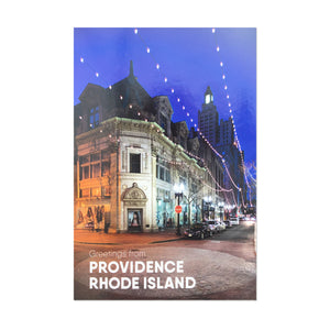 "postcard photograph of iconic downtown Westminster Street lit up at night with white text on the bottom that reads ""Providence, Rhod Island"""