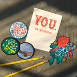 greeting card, patches, pencils, and a sticker laying in soft natural light