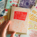 "stack of greeting cards featuring one with a flower patter which reads ""you're the best mom I've ever had"""