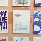 "greeting card which reads ""you'll be back on your bullshit in no time"" featuring an illustration of a person in a body cast giving a thumbs-up shown hung on a wall amongst other cards"
