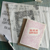 "greeting card with pink leaf pattern and red text which reads ""you are my happy place"" pictured with design sketches and a pen"