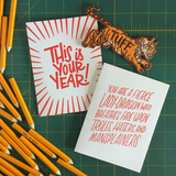 two white greeting cards with red text pictured with pencils and a tiger patch