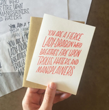 "hand holding a white greeting card with red text which reads ""you are a fierce lady-dragon who breathes fire upon trolls, hater, and mansplainers"" above design sketches"