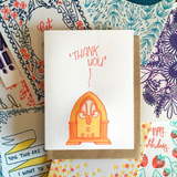 "white greeting card with an illustrated old fashioned radio, printed in orange, beath hand-lettering that reads ""thank you"" photographed on top of an assorment of other Frog & Toad Press greeting cards"