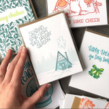 "white greeting card with a blue and teal illustration of an a-frame cabin and tree line of pines. hand lettering above the house reads ""sending love + light this holiday season"" shown as a boxed set hand-held amongst other boxed holiday cards"