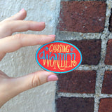 "A hand holding an oval shaped red patch with ""chasing wonder"" in yellow and blue against a brick wall."