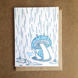 "white greeting card witn an illustration of a snail hiding from the rain beneath a mushroom next to hand-lettering that reads ""thank you"""