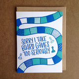 "white greeting card with a patterned teal and blue board game track and game piece illustration surrounding hand-lettering that reads ""sorry i take board games too seriously"""
