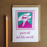 "greeting card with a pink and teal illustration of Gilbert Stuart which reads ""you're old, but like, cool old"" shown next to a pencil"