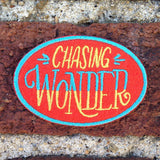 "An oval shaped red patch with ""chasing wonder"" in yellow and blue against bricks."