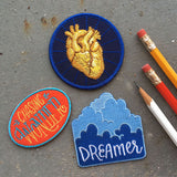 "Three patches. A blue patch with a gold anatomical heart, An oval shaped red patch with ""chasing wonder"" in yellow and blue, and clouds with dreamer below them."