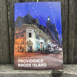 "postcard photograph of iconic downtown Westminster Street lit up at night with white text on the bottom that reads ""Providence, Rhod Island"" photographed in front of a fence"