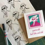 "greeting card with a pink and teal illustration of Gilbert Stuart which reads ""you're old, but like, cool old"" shown with design sketches and a pen"