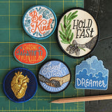 "6 patches. From left to right, a white patch with orange ""be kind"" and blue flowers, a white patch with an eagle holding an olive branch and ""hold fast"" above it, An oval shaped red patch with ""chasing wonder"" in yellow and blue, a blue patch with gold anatomically correct heart, a hand holding a paw with ""friend to strays"" above it, and a cloud patch with ""dreamer"" below."