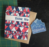 "white greeting card with a red and blue illustrated triangles pattern and hand lettering that reads ""thank you"" photographed with a blue could ""dreamer"" patch"