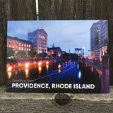 "postcard photograph of Waterfire occuring on the Providence canal at dusk. white text on the bottom reads ""greetings from providence, rhode island"""