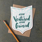 "badge-shaped greeting card with a light blue illustration of a mountain range behind green hand-lettering that reads ""nothing ventured nothing gained"" photographed with a pencil"