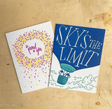"white greeting card featuring an illustration of two penguins riding in a hot air balloon. hand-lettering on the balloon reads ""sky's the limit"" pictured with a ""so proud of you"" greeting card"