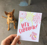 "Greeting card and kraft paper envelope. Text reads, ""Let's celebrate!"" Illustration of fireworks with dog below, shaking, holding a sign that says, ""quietly."" Photographed hand-held with a dog viasble in the background"