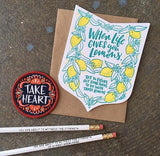"Die cut badge-shaped greeting card that reads ""when life give you lemons, try to figure out something to do with those lemons"" in teal text surrounded by illuatrated lemons and leaves photographed with a ""take heart"" patch and two white pencils"