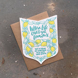 "Die cut badge-shaped greeting card that reads ""when life give you lemons, try to figure out something to do with those lemons"" in teal text surrounded by illuatrated lemons and leaves"
