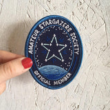 "A person holding the An oval iron on patch that reads ""amateur stargazer society official member"" with a star connected like a constellation above a planet against a textured wall."