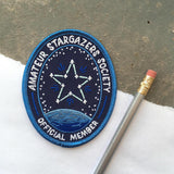 "An oval iron on patch that reads ""amateur stargazer society official member"" with a star connected like a constellation above a planet next to a silver pencil."