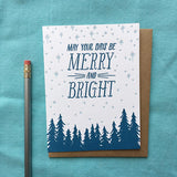 "white greeting card with a navy pine tree design beneath hand-lettering that reads ""may your days be merry and bright"" amongst a pale blue starry sky photographed with a pencil"