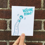 "Greeting card and craft envelope that reads ""welcome peanut!"" in teal, hand-written type in upper right corner. Illustration of elephant trunk shaking rattle. Photographed hand-held in front of a brick wall"