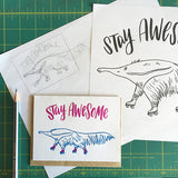 "white greeting card with an illustrated ant-eater on rollerskates beneath hand-lettering that reads ""stay awesome"" photographed with a pencil and design sketches"