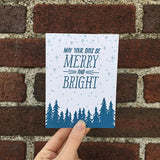 "white greeting card with a navy pine tree design beneath hand-lettering that reads ""may your days be merry and bright"" amongst a pale blue starry sky photographed hand-held in front of a brick wall"