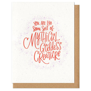 "white greeting card with red hand lettering that reads ""you are like some sort of mythical godess creature"""