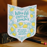 "Die cut badge-shaped greeting card that reads ""when life give you lemons, try to figure out something to do with those lemons"" in teal text surrounded by illuatrated lemons and leaves photographed amongst studio equipment"