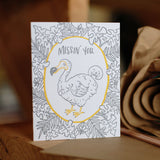 "Greeeting card and kraft paper envelope. Grey, illustrated tropical leaves surrounding dodo bird with text above him that reads, ""Missin' you."""