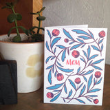 "white greeting card with red  hand-lettering that reads ""mom"" surrounded by red and green illustrated tulips pictured with a potted plant"