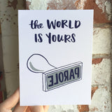 "white greeting card that reads ""the world is yours"" in navy text above an illustration of a ""parole"" stamp photographed being hand-held infront of a brick wall"